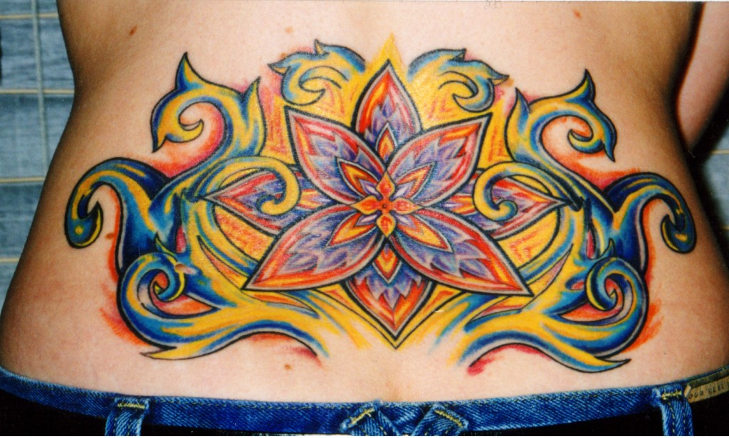 custom color glowing flower lower back tattoo for women at Majestic NYC