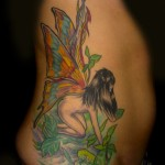 colorful naked fairy with butterfly wings in forest clearing side tattoo by Adal