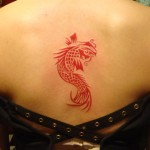 color red tribal fish tattoo on back by Majestic