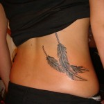 Custom black and grey realistic feminine double feather tattoo on woman hip by NYC artist Adal at Majestic studio Tribeca Manhattan