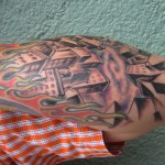 realistic bird's eye view of a city arm tattoo with flames by Adal