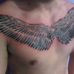 latin text wing chest tattoo by Adal at Majestic