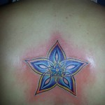 colorful abstract flower tattoo design on upper back Majestic Tattoo NYC