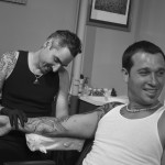 Adal tattooing a sleeve at Majestic - black and white