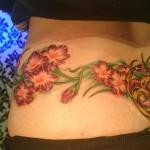 flowers snake infinity lower back neverending story tattoo